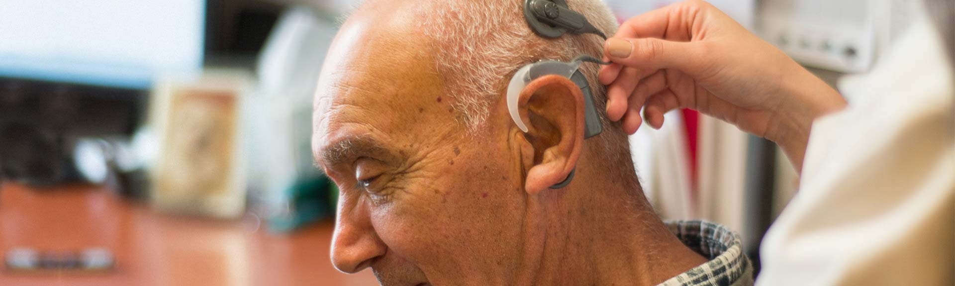 Hearing aid technology on an elderly gentleman at New York Eye and Ear Infirmary of Mount Sinai