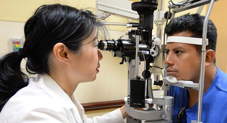 Female Ophthalmologist exams male patient with a slit lamp for corneal disease and cornea treatment