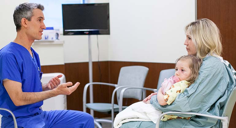 Dr. Gregory Levitin, discussing with female child patient and mother about vascular birthmark treatments